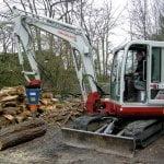 Hier spaltet eine Takeuchi Baumaschine mit einem aufgesetzten DKS170 einen dicken Holzblock
